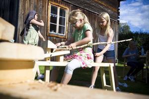 Elsa Alnehem Granström och Klara Nyberg hjälps åt att tälja bort barken på den gren som ska bli kroppen till deras gemensamma docka.