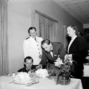 1953. Ett bord dukas på Klippan. Visst blir man lite nyfiken på vad de olika personerna på bilden har för roll.
