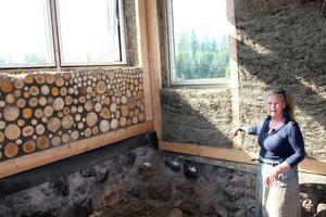 Marjo Marthin visar olika byggnadstekniker. Den ena väggen är isolerad med halmbalar och den andra av staplad vedkubb.