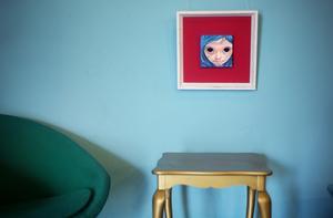 Snurrfåtölj, guldbord och konst.