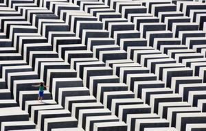 En kvinna står på ett av de 2711 block som utgör minnesmonumentet över Europas mördade judar. Verket är skapat av Peter Eisenman och finns i Berlin. Foto: Gero Breloer/TT