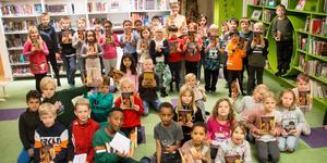 """Ett gäng glada tvåor fick på fredagen en bokgåva från biblioteket i Norberg. Längst bak i gul klänning står initiativtagaren, bibliotekspedagog Pia Carlsson. Boken som tvåorna fick heter """"De stulna barnen"""" och är en fantasybok av Jo Salmson."""