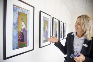 Helene Åkerström Hartman visar Lillebi Habans målningar med en folkdräkstklädd kvinna  som på varje bild har olika nationaliteter.