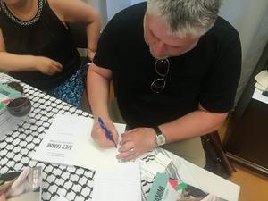 Paul Morris signerar sin bok under boksläppet på Palestinas ambassad i Stockholm.Foto: Håkan Galmén