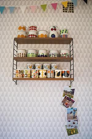 Porslin och keramik med vackra mönster är verkligen något som Victoria gillar. Här på hyllan i matrummet trängs fina  syltburkar från finska Arabia med muggar av Victorias favoritdesigner Orla Kiely. Nedanför hänger familjefotografier från tiden i Brighton.