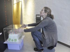Ulrika Björck plockar fram en låtsastårta – en av alla prylar som ingår i matteutställningen.