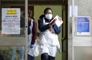 En sjukvårdsarbetare i Kapstaden, i det virusnedstängda Sydafrika, spritar händerna.