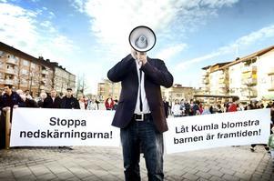 """Inget aprilskämt. När Magnus Thorstensson kallade i megafonen tätnade leden av Kumlabor bakom parollerna """"Stoppa nedskärningarna"""" och """"Låt Kumla blomstra, barnen är framtiden"""". Uppskattningsvis kom mellan 600 och 700 personer till torget för att protestera mot politikernas sparplaner, som i slutändan visade sig bero på ett bokföringsfel. arkivbild: GÖRAN KEMPE"""