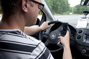 Förbjudet. Från och med den 1 december får man inte använda mobilen på ett trafikfarligt sätt i trafiken.