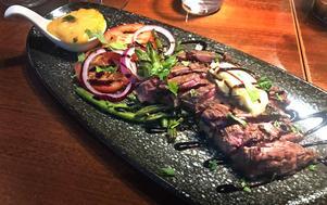 Den grillade flanksteken visar sig vara en rejäl bit mörat kött som serveras medium rare precis som vi beställt det.
