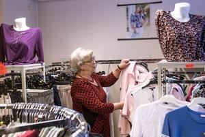 Monica Sjödin plockar bland kläderna som hon gjort i så många år.