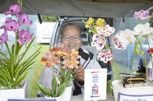 Pratoom Jonsson bakom sin blomsterprakt av bröddegsbakade orkidéer.