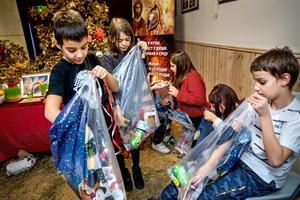 Novak Ramovic, 7år, Sofija Kulijadin, 9 år, och Filip Ramovic, 11 år undrar vilka söta julklappar som gömmer sig i påsarna.