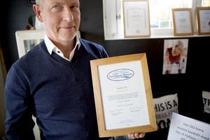Lars Carlstrand, ordförande i Svensk massage, visar upp Sandra Sälls diplom.