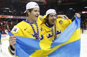 Filip Forsberg och matchvinnaren Mika Zibanejad firar med den svenska flaggan efter JVM-finalen mot Ryssland.