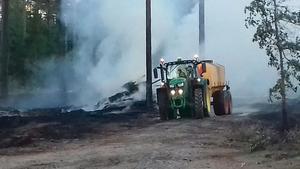 Niklas Lorenz på Åsby lantbruk blöter ner brandområdets ytterkanter med hjälp av en dyngspridare som fyllts med vatten. Foto: Bo Sundstedt.