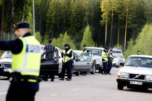 """Få se här...Polisaspiranten Malin Köhler kontrollerar Kaj Åkerbloms körkort och nykterhet. Röret som han blåste i blev sedan biljetten ut från kontrollplatsen. """"Att det skulle vara så många poliser här hade jag inte räknat med"""", säger han och skrattar."""