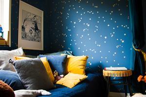 Stjärntapeten pryder väggarna i sovdelen som ramas in av  tunga sammetsdraperier.