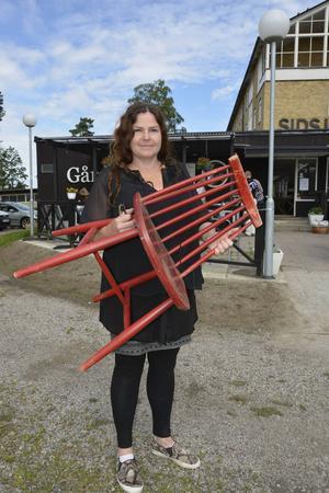 Dekoratör Ingela Lundwall håller upp ytterligare en stol till samlingen.