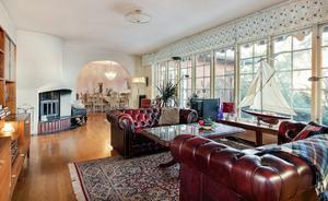 Vardagsrummet före. Med skinnsoffor och orientalisk matta.