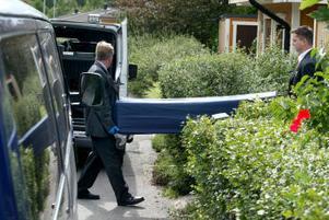 Här bärs den döda kvinnan ut ur parets bostad i Granloholm.