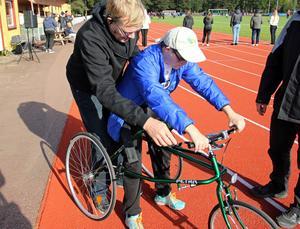 Jan-Olov Fredborg visar Emil Andersson hur han ska göra med den nya racerunning-cykeln.
