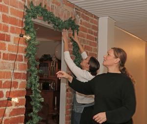 Alice och Elizabeth Genberg sätter upp julgirlanger i hallen.