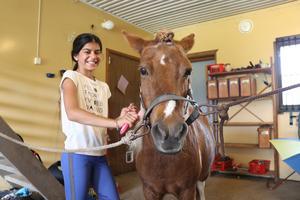 Lägerdeltagare Elahe tar hand om hästen Freya efter dagens ridpass.