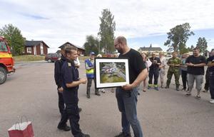 Pierre Hedlund, räddningstjänsten Särna, får tillbaka nycklarna till brandstationen och en tavla från händelsen av räddningsledare Johan Szymanski.