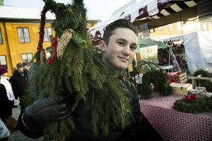 Johan Samuelsson bär en julbock av gran som Maria Wikström från Nora gjort. Hon säljer ungefär 25-30 stycken bockar varje år vid marknaden i Falun.