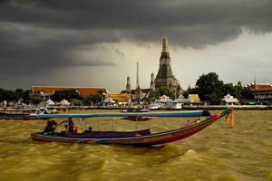 Långsvansbåt på Chao Phraya-floden med Skymningstempel - Wat Arun - i bakgrunden. Några minuter efter att bilden tagits börjar åskregnet.