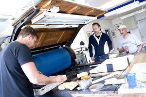 Jordi Arkö (med basker), konstkonsulent på Länskonst Dalarna och konstnären Henry Graham Hermunen från Helsingfors tittar på när P.O Westman förbereder hans sten för tryckning.