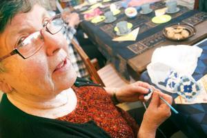 Det är ok att virka på stickkafét i Bergsjö också, så Britt Edberg virkar mormorsrutor i vitt och blått.