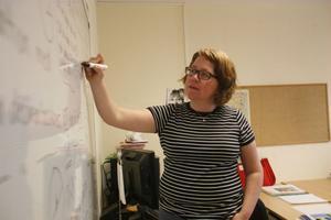 Helena Andersson använder sig av whiteboardtavlan för att förklara hur man kan räkna ut omkretsen.