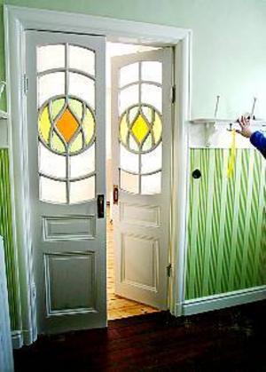 Foto: ANNAKARIN BJÖRNSTRÖM Solig hall. Det gula och gröna i glaset går igen lite varstans i huset. Ett rum har milt gula väggar, ett annat ljust gröna medan övriga väggar fått beigevita nyanser. Hyllorna med knoppar för hattar låg i källaren men pryder nu åter sin plats i entrén. Här är panelen grön men i resten av huset är den gråvit.