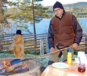 Storvästförsedde Börje Sander värmer sig och kolbullepannan vid elden. I bakgrunden ses Torbjörn Lindgrens skulptur Drullasbäckstrollet.