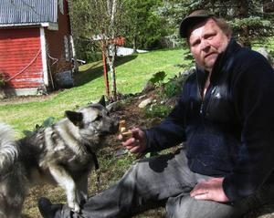 Örjan Thalén med sin son Viktors gråhund som väckte Örjan som hann ut för att rädda det mesta av innehåller i sin branddrabbade verkstad.
