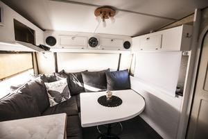 Matplats, sällskaplplats och tv-höran i ett. Med nedrullad projektorduk, som egentligen är en mörkläggningsgardin, och med projektor fastborrad i en skåpslucka har husvagnen en filmhörna. Bordet är hemmagjord och vridbart och stolsbenet är en ganmal barstol från Hotell Knaust i Sundsvall.