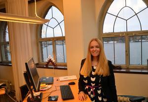 Tre stora fönster ramar in utsikten över Riddarholmen och andra klassiska Stockholmsvyer från Johannas arbetsplats belägen på det tredje planet i den enorma byggnaden