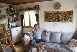 Stugan har en yta på bara 35 kvadratmeter. Ändå finns där allt som behövs för att leva gott. Här är det Lars Eriksson som sitter i bäddsoffan.