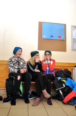 FNITTRAR. Mikael Jansson, Emma Zetterberg och Linnea Ljungqvist fnittrar på bänken i hallen.