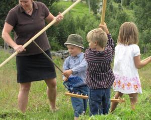 Katrin Hjort lär Erik Odén, Olle och Mina Salomonsson hur det går till att kratta gräs under slåttern.