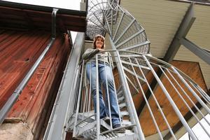 Susanne Runesson i spriraltrappan som leder ett tiotal meter upp till den översta våningen.