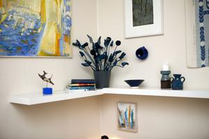 Liv i mörkt hörn. Sovrummets detaljer binds samman av blått. I det mörka hörnet, där växter inte trivs, bidrar målade strån med liv.