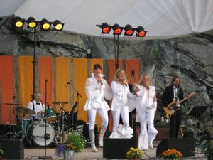PrimaDonnor, Charlott Strandberg, Gunilla Backman och Sussie Eriksson, här flankerade av trummisen Peter Milefors och gitarristen Magnus Bengtsson i Svenska Lyxorkestern, framträdde på lördagskvällen för en entusiastisk publik vid den årliga konserten i Stenbrottet i Gåxsjö.   Foto: LO Rindberg.
