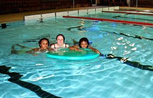 Badglada tjejer. Nadia Aden och Azhar Mohamed, med kompisen Jenny Fredriksson i mitten, tar ett dopp i bassängen på damernas egen baddag på Hällåsen.