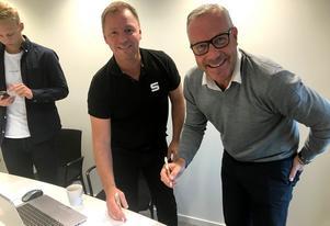 Urban Nyberg och Petter Lundgren skriver på kontraktet. Till vänster SAIK-målvakten Jesper Sundving som även jobbar som kommunikatör på SAIK-kansliet.