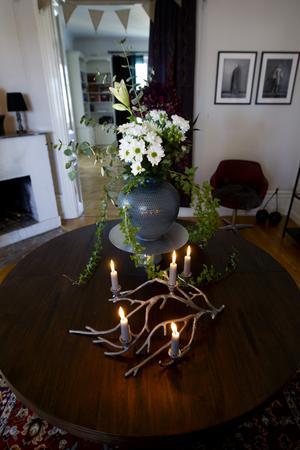 Redan i hallen möts man av ett maffigt bord med tända ljus och ett ståtligt blomsterarrangemang som Erika komponerat ihop själv av buketter och en krukväxt.