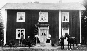 Så här såg Stinas barndomshem ut innan Stina var född. På bron sitter Stinas farmor och mamma. Pappan håller i hästen och syskonen Annie och Hedda finns också med.