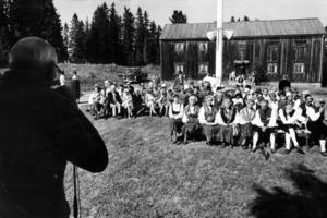Den här bilden, från firandet av hembygdsdagen och med hembygdsgården i bakgrunden,  är tagen i augusti 1969. I förgrunden Elias Jonsson som spelade Lapp-Nils-låtar på munspel. Lapp-Nils, som egentligen hette Nils Jonsson, var en samisk spelman, född 1804 i Hallen och död 1870 i Offerdal.